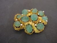 ANDREW GRIMA BROOCH SET IN GOLD WITH CUT EMERALDS